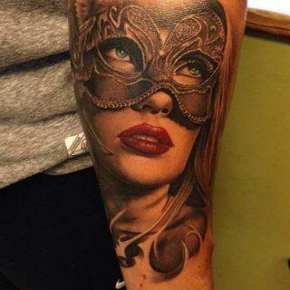 Цветная татуировка лицо в маске на внутренней стороне руки