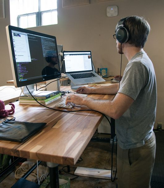 DIY adjustable standing desk built with iron pipes and Kee Klamp fittings.