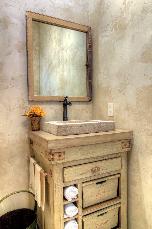 une commode en bois vieilli à tiroirs et un vasque en pirre dans la salle de bains