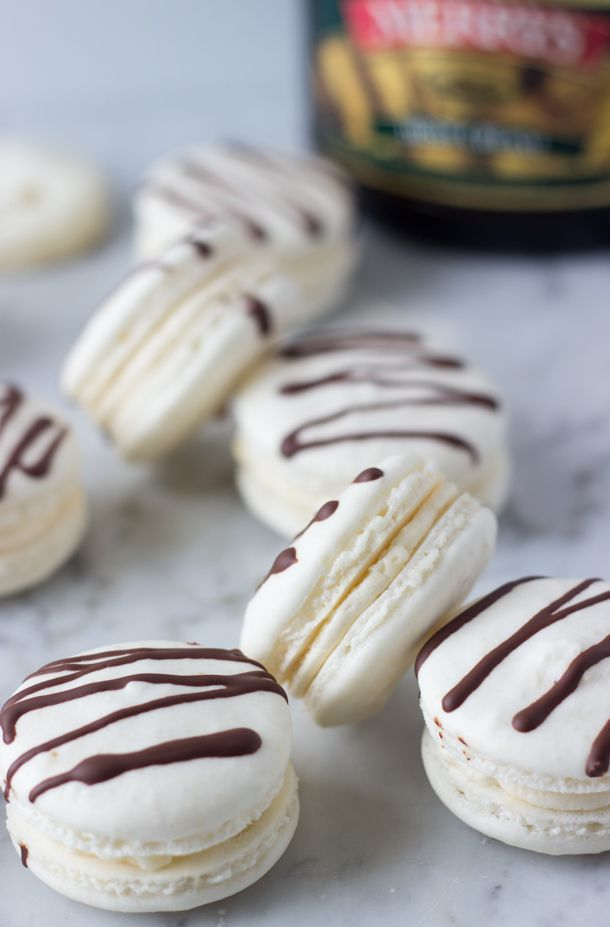 Celebrate St Patrick's Day with these Irish Cream Macarons - crunchy macaron shells with a sweet Irish Cream filling and chocolate drizzles.