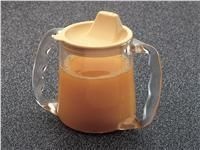 The caring mug is a clear, lightweight mug with a wide base and two angled handles.The separate lid has a feeding spout with three small holes for the flow of fluid. It is suitable for adults, and is dishwasher and microwave safe.
