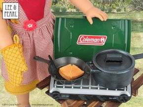 """We lovethis ultra-realistic, 18 Inch doll Coleman®️️ camp stove from Sophia's.It comes with plenty of food and a nifty saucepan,but we thought it needed a matching cast iron pot — so we made one!Our new pot (on the right) started out as a plastic dollar store toy. But you'd never know afterour realistic paint job.For this easy """"cast iron"""" paint tutorial, visit the Lee & Pearl July 4th Pictorial / Tutorial in our Newsletter Archive at http://leeandpearl.com/pictorial_2015_July4.htm"""
