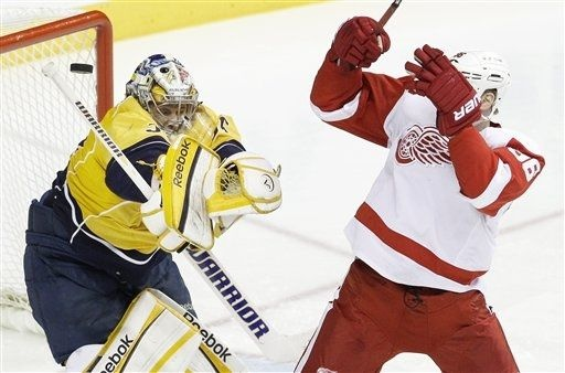 A shot sails past Nashville Predators goalie Pekka Rinne, left, of Finland, and Detroit Red Wings left wing Tomas Holmstrom (96), of Sweden, in the third period of Game 1 of a first-round NHL hockey playoff series on Wednesday, April 11, 2012, in Nashville, Tenn. The Predators won 3-2. (AP Photo/Mark Humphrey)
