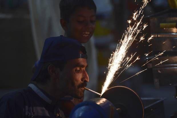 Σιδηρουργός στο Rawalpindi, του Πακιστάν, ανάβει το τσιγάρο ρου καθώς ακονίζει στον τροχό ένα μαχαίρι. (Farooq Naeem/AFP/Getty Images)