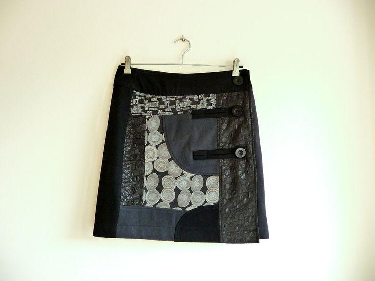 Falda negra de Patchwork. Falda negra y gris con estampados. Falda corta. Desigual.  Se abrocha al lateral con botones. Esta en perfecto estado  Medidas:  Cintura 81cm  Largo total 47cm