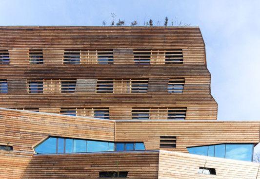 Der leicht geschwungene Baukörper ist vollständig mit Lärchenholz verschalt und verjüngt sich über fünf Geschosse nach oben