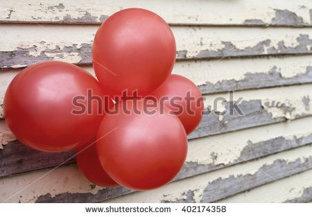 Red balloons on rustic paint peeling wall