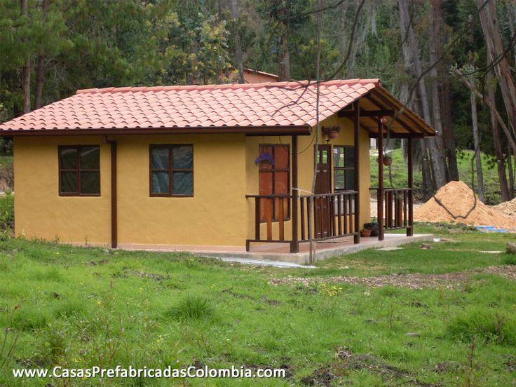 Casa pequeña de un nivel en teja de barro, puertas y ventanas metálicas, acabado de pañete en paredes, barandas en madera.