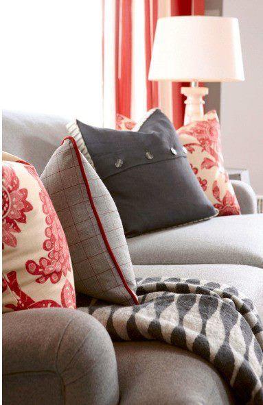 Kleurloze woonkamer fleur je snel op met rode kussens.