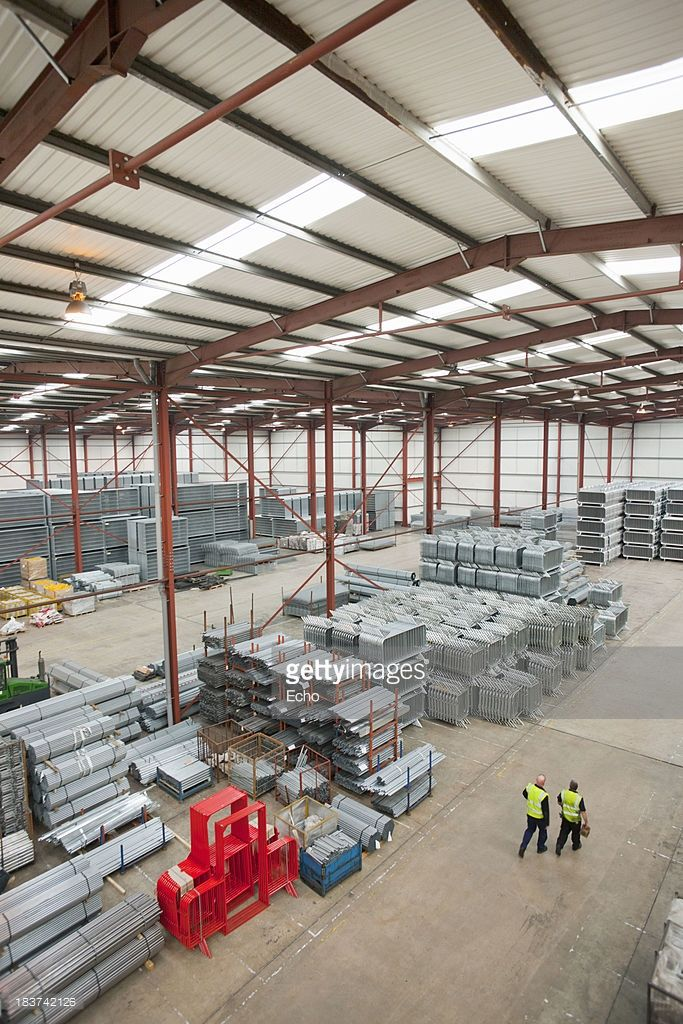 Stock Photo : Workers walking through warehouse with steel tubing and finished safety barriers