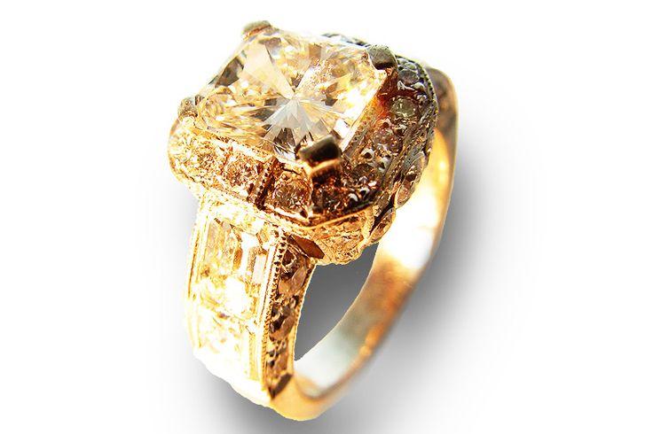 RADIANT CUT DIAMOND IN DIAMOND ENCRUSTED 18 KARAT GOLD RING.