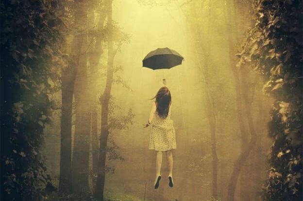 ragazza vola appesa all'ombrello