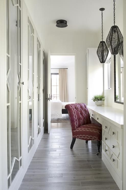 Chic yet simple long Mediterranean dressing room is illuminated by staggered black lanterns hung above a white built in makeup vanity accented with ornate drawer fronts and seating a purple roll back vanity chair facing a black framed mirror.