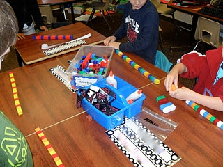Patterning Musical Chairs: Pass out manipulatives to students to create a pattern on their desk. Each student creates only 3 units of their pattern -- repeating or growing pattern. Extra manipulatives stay on table for the game. Play music as students travel around the room. When you stop the music, each student finds a desk -- must figure out the pattern at that desk and then add 1 more unit onto the pattern. At the end > return to their original desk & check their own pattern to see if it…