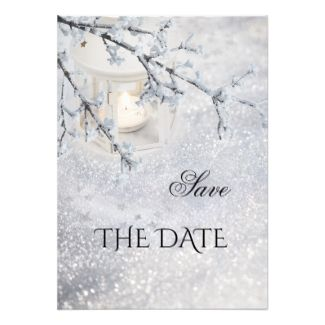 Save the Date card featuring a candle lit lantern in a sparkling snow winter wonderland