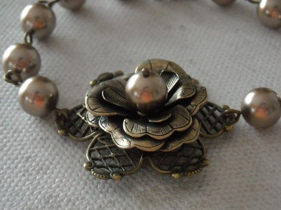 Stylish bracelet.  This vintage style bracelet features a beautiful antiqued brass rose flower adorned by a bronze pearl