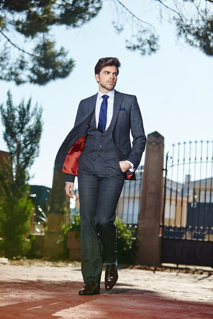 Men's dark grey plaid tailored three-piece suit with vibrant contrast lining.