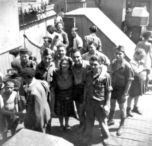 """Buchenwald Children"" on a ship en route to Eretz Israel, 1945. In the center of the photograph is a non-Jewish counselor from OSE, France."