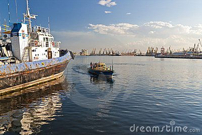BLACK SEA, CONSTANTA, ROMANIA - AUGUST 03, 2011 - Few sailors on small boat returns to docks passing by an anchored towboat on August 03 2011 in Constanta port. Many big cranes in the shipyard at horizon.