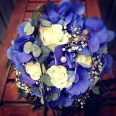 blå hortensia, vita rosor, brudslöja, läderblad, strån och hjärtan på tråd.