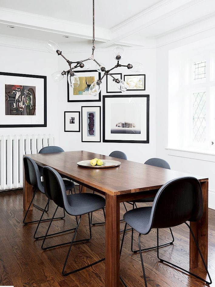 Modern dining space with Sputnik chandelier and gallery wall.