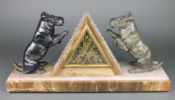 Lot 727, A French Art Deco 8 day striking mantel clock contained in a 2 colour marble pyramid shaped case, the gilt diamond shaped dial with Arabic numerals and flanked by a pair of spelter West Highland Terriers, est £60-90