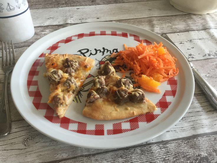 Pizza met gehaktballetjes en een wortelsalade ernaast