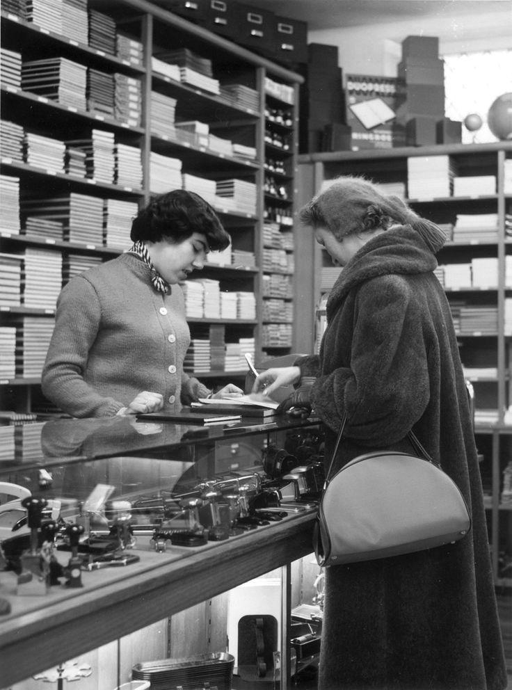 Klant aan de toonbank bij kantoorboekhandel (winkel in kantoorartikelen), 1956.