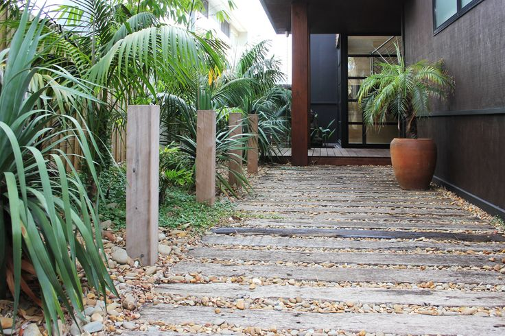 Natural sleeper and gravel path with vertical timber uprights leading to front door.