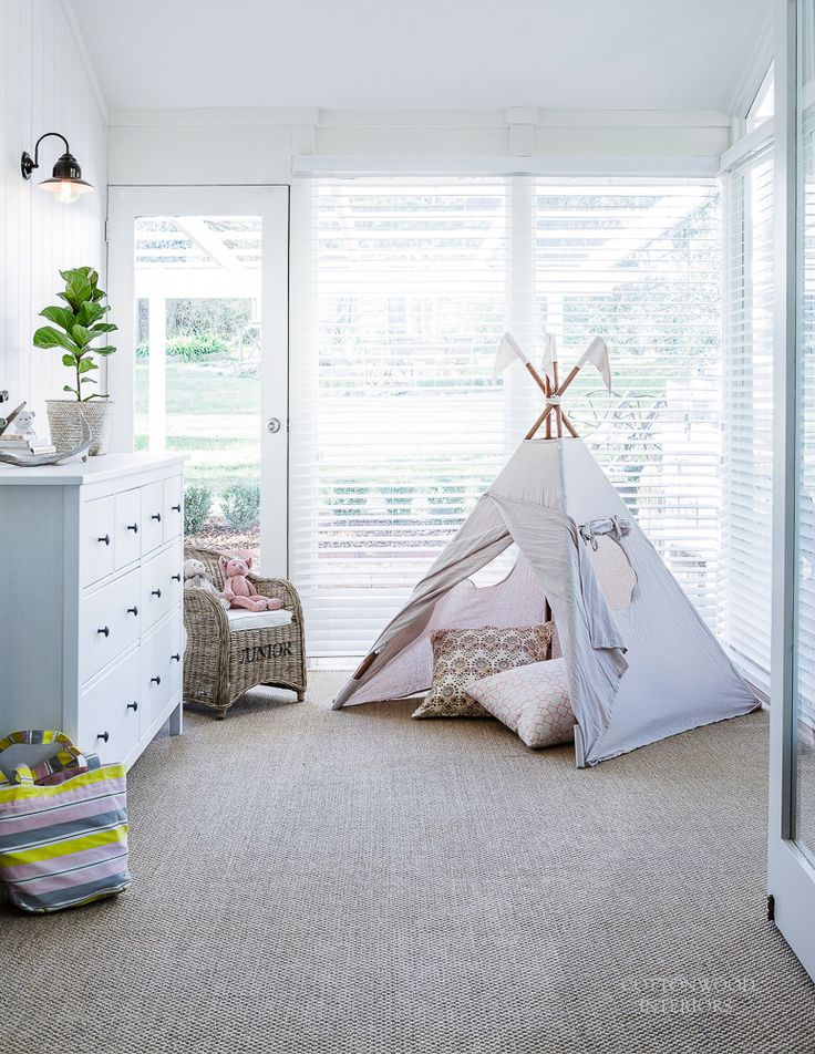 Playroom with sisal carpet, blush pink linen teepee, chest from Ikea, and rattan mini chair   Cottonwood Interiors. Photo by Maree Homer.