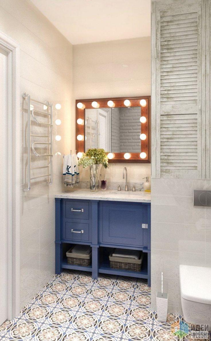 Зеркало в деревянной раме с лампочками напоминает зеркала в гримерных. Под раковиной - синяя тумба с местом для хранения банных принадлежностей.