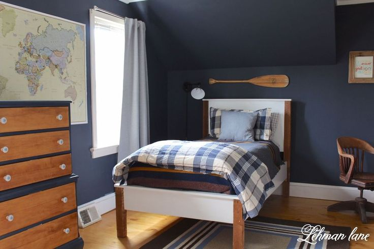 Navy globe trotter themed bedroom is a fun classic style. Great wall color to accent the light floors.