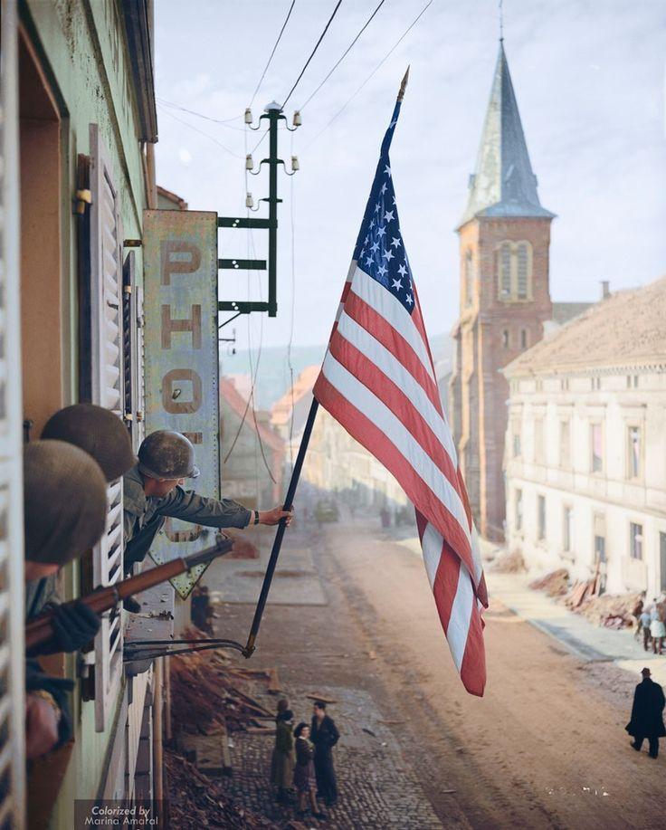 1945년 프랑스 소녀가 몰래 만든 성조기 깃발을 들고 있는 토마스 H. 그라한 대위
