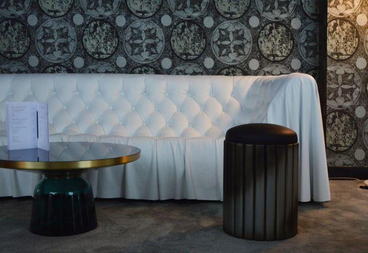 Di fronte alla reception dell'hotel parigino La Demeure, il duo di designer Flavie+Paul ha creato un salone accogliente, con tende leggere dal décor optical che rivestono le pareti in maniera avvolgente. Arredi tutti su misura e sotto i piedi una morbida moquette grigia