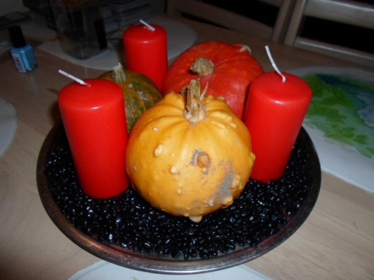 Halloween decoration with black stones, orange candles and little pumpkins.