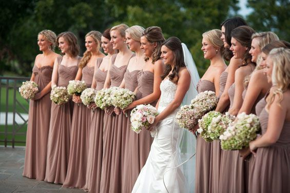 Eleven bridesmaids and two maids-of-honor wore latte floor-length dresses and held bouquets of hydrangeas and white Majolica spray roses.