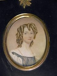 Alfred Edward Chalon, circa 1825 A young girl with her hair dressed in ringlets wearing a dark blue tunic with white chemise with puff sleeves Set in gilt– mounted rectangular papier mache frame    Dimensions: Oval, 3inches high