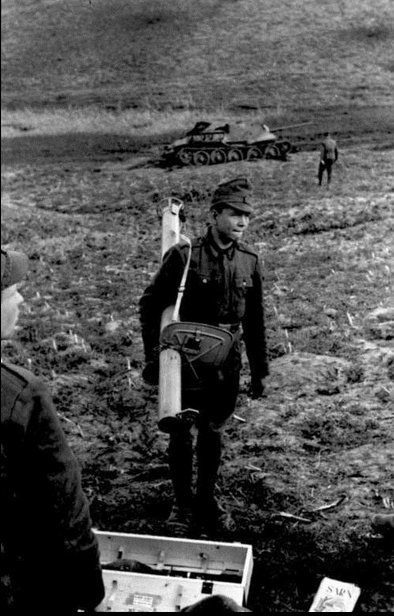 Romanian soldiers with RPzB.54 Panzerschreck on the background destroyed Soviet SU-85 self-propelled guns.