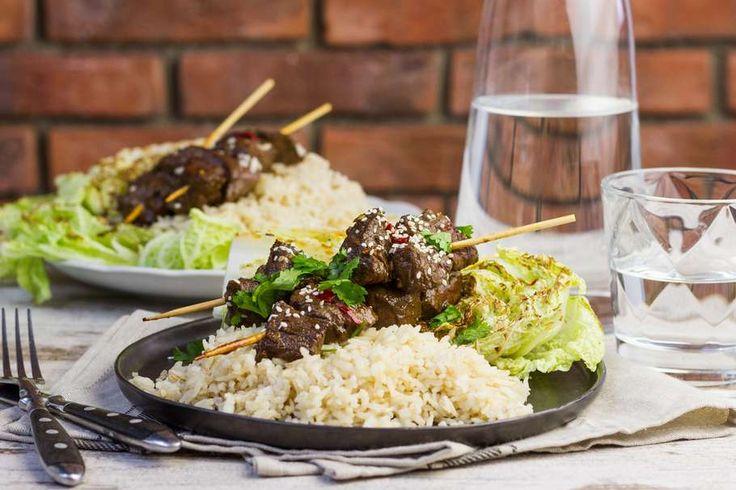 Recept voor rundersaté voor 4 personen. Met zout, olijfolie, peper, satéprikkers, biefstuk, rijst, Chinese kool, sojasaus, ketjap manis, rode peper, knoflook, sesamzaad en koriander