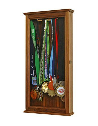 Medal Wall Cabinet-Walnut Hardwood *Made in the USA*. You will find many products available on-line for hanging medals, but none of them are made with the care and quality of this cabinet which is made in our Oregon workshop. This is the ultimate complement to the athlete's accomplishments! Constructed of solid Walnut hardwood with a glass door to protect contents. Finisher medals hang from 3 hooks. Cabinet comes equipped with brass door hinges and a high quality door latch. It is…