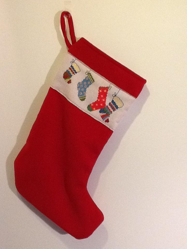 Kerstsok van rode stof met geborduurde rand.