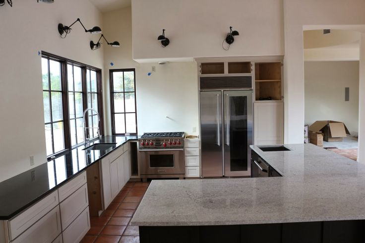 bianco montahna granite, black granite countertops, wolf range, marvel refrigerator, glass door refrigerator, kitchen without upper cabinets
