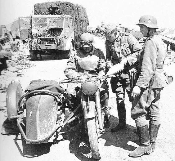 German troops study a map amid the wreckage left behind by evacuated British troops, Dunkirk, France, May/June 1940. The motorcycle is the eternal BMW R6.