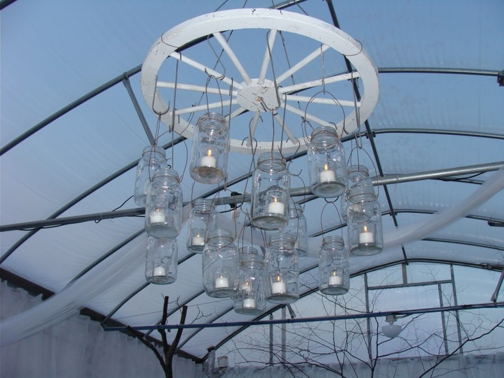 Mason jar chandelier made with wagon wheel for the wedding.
