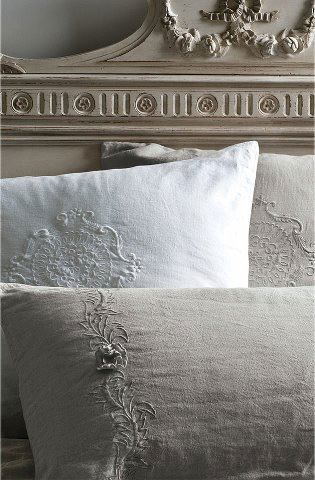 stunning antique linen pillow covers. taupe, white on a fabulous French carved bed .