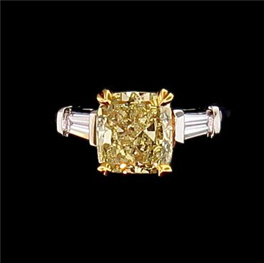 Gloriously sunny 2.10 carat cushion-cut fancy yellow diamond ring with accent baguettes. 14 karat yellow and white gold.