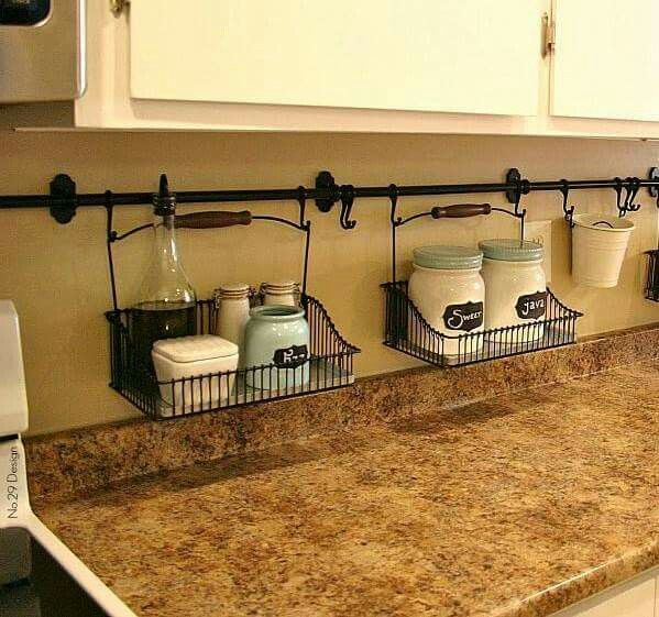 By hanging curtain rods and holders, matching S hooks and coordinating baskets you're able to eliminate the clutter on your kitchen counters. Easy for clean ups! Love this idea!