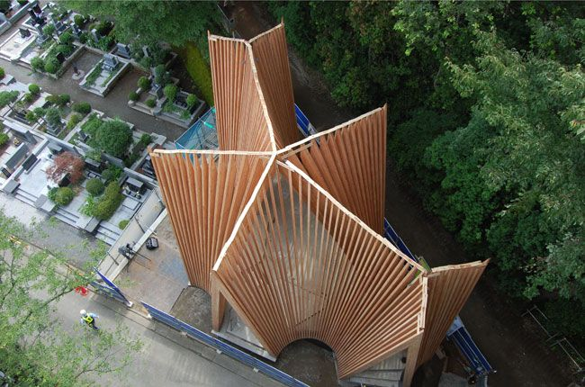 The chapel is clad with rough aluminum tiles that deter unsightly sap drippings. Cast in six rectangular shapes, the malleable plates were bent by hand to accommodate the building's curves.