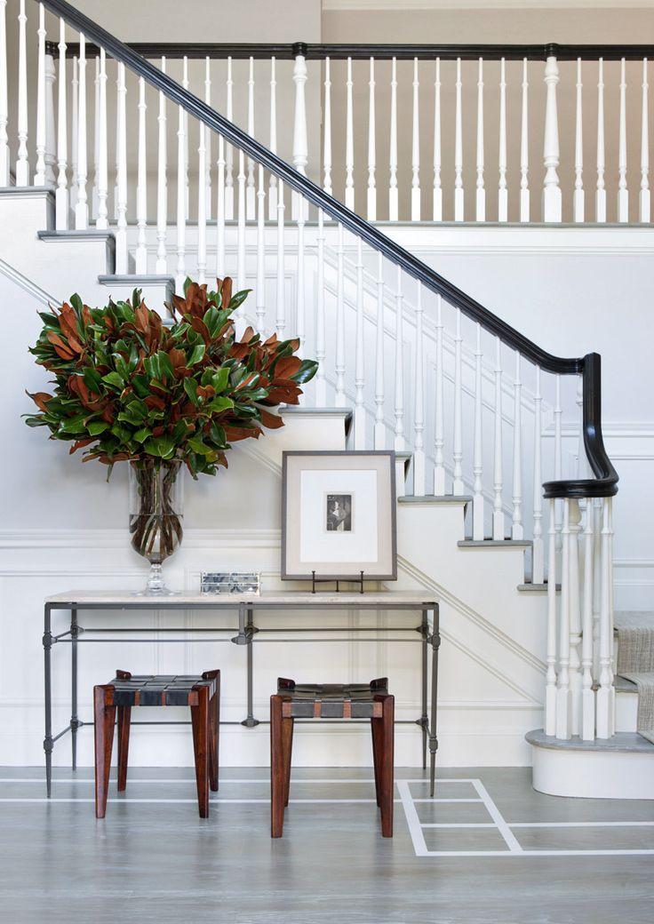 A lush arrangement of magnolia leaves creates a verdant focal point in a Long Island, New York, home's monochromatic entryway.