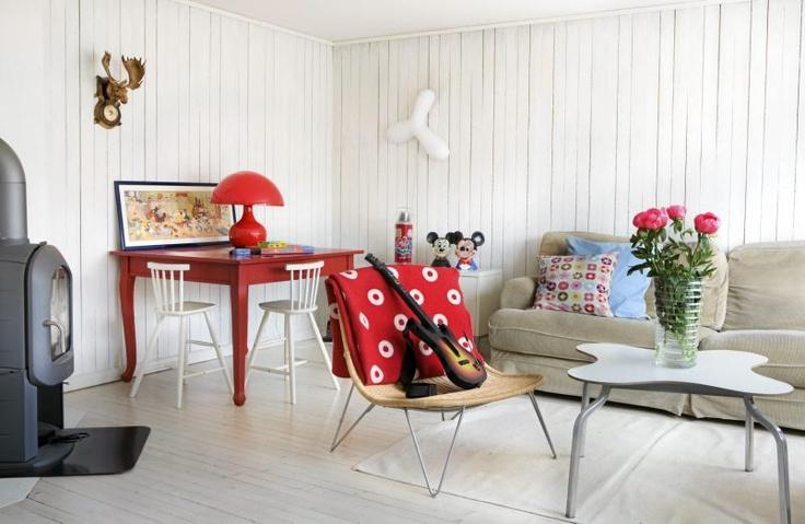 Eieren har tillatt lek å ta plass i innredningen. En glede for både barn og voksne. Sofabordet er fra Verket Interiør, det røde bordet er kjøpt brukt og senere malt. De hvite pinnestolene for barn er fra Ikea, mens lampen på bordet er et bruktfunn.
